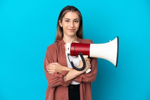 Młoda kobieta kaukaska na białym tle trzymając megafon i uśmiechnięte