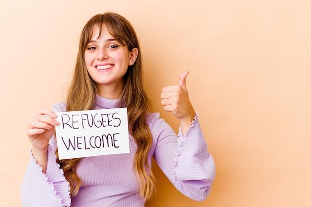 Młoda kobieta kaukaska trzyma afisz witamy uchodźców na białym tle uśmiechnięty i podnoszący kciuk do góry