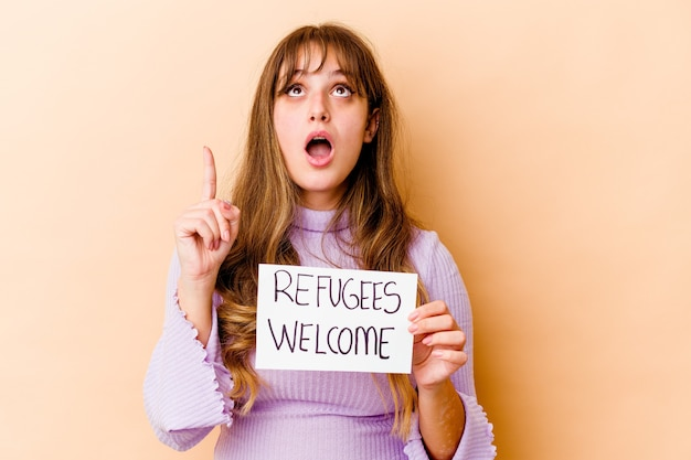 Młoda kobieta kaukaska trzyma afisz witamy uchodźców odizolowane, wskazując do góry z otwartymi ustami.