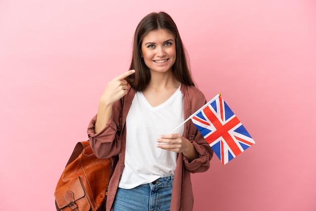 Młoda kobieta kaukaska trzyma flagę zjednoczonego królestwa na białym tle na różowej ścianie gestem kciuki do góry