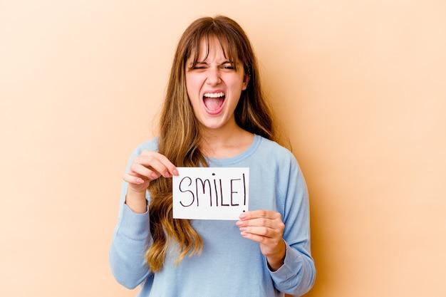 Młoda kobieta kaukaska trzyma tabliczkę smile izolować