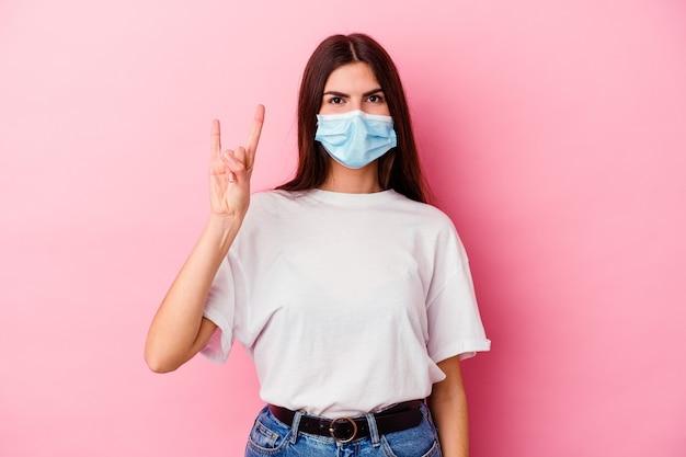 Młoda kobieta kaukaska ubrana w maskę wirusa na białym tle na różowej ścianie przedstawiający gest rogów