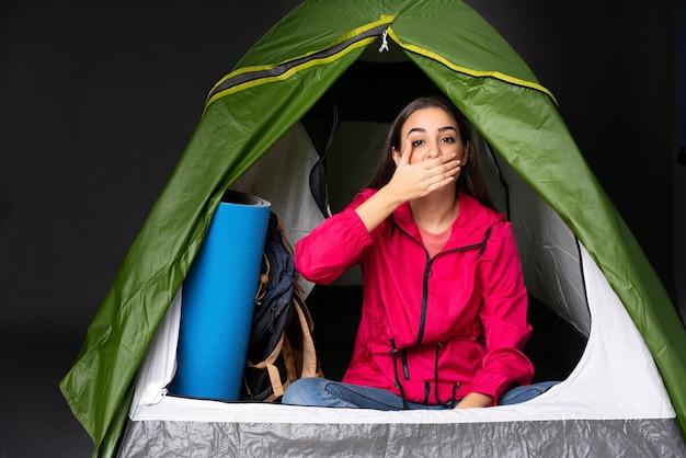 Młoda kobieta kaukaska wewnątrz namiotu kempingowego, obejmujące usta rękami