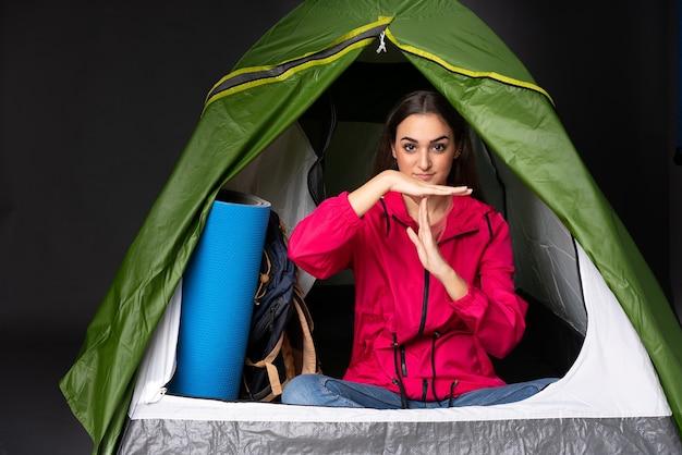 Młoda kobieta kaukaska wewnątrz namiotu kempingowego zielonego, czyniąc gest czasu
