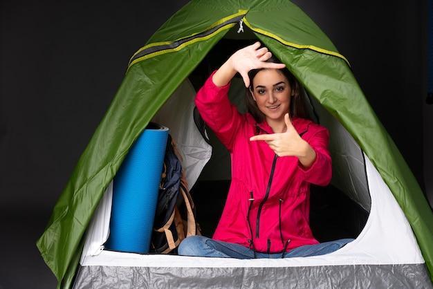 Młoda kobieta kaukaska wewnątrz namiotu kempingowego zielony, koncentrując się na twarzy