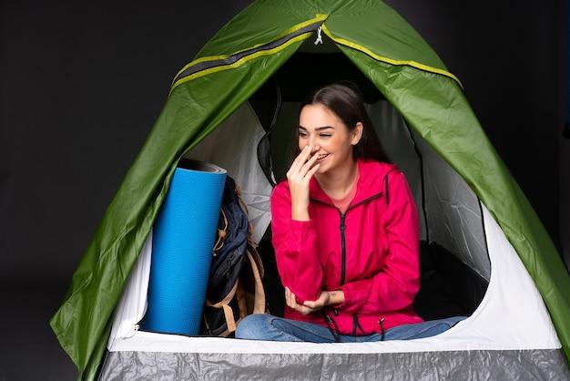 Młoda kobieta kaukaska wewnątrz zielonego namiotu kempingowego dużo się uśmiecha