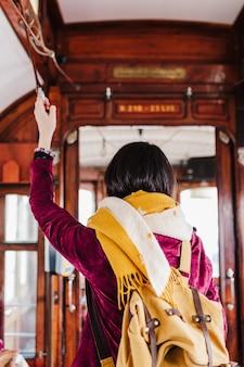 Młoda kobieta kaukaski backpacker zwiedzanie porto widoki stojąc w pociągu. koncepcja podróży