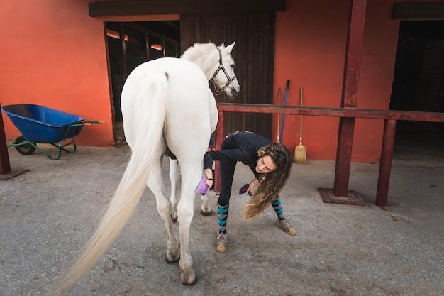 Młoda kobieta kaukaski czyszczenie i przygotowanie konia.