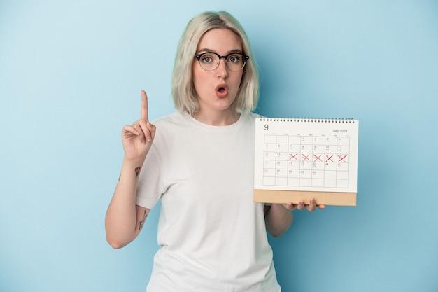 Młoda kobieta kaukaski gospodarstwa kalendarz na białym tle na niebieskim tle o jakiś świetny pomysł, pojęcie kreatywności.