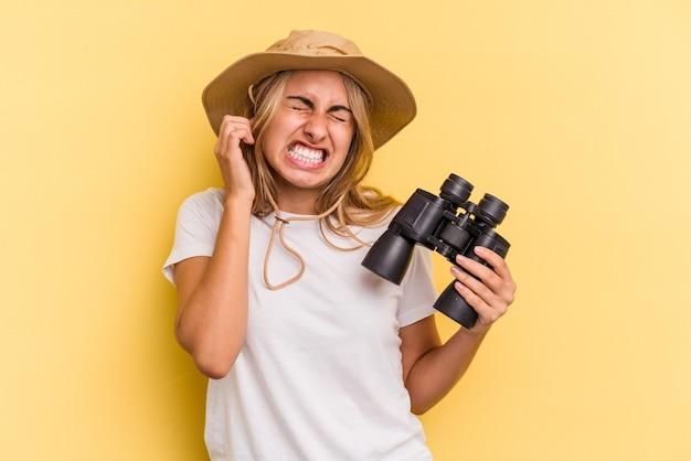 Młoda Kobieta Kaukaski Gospodarstwa Lornetki Na Białym Tle Na żółtym Tle Obejmujące Uszy Rękami. Premium Zdjęcia