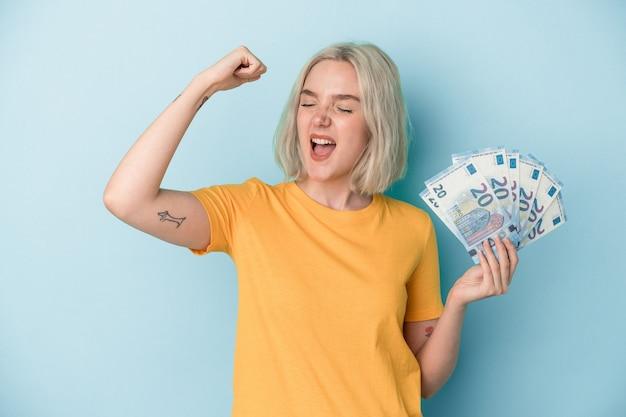 Młoda kobieta kaukaski gospodarstwa rachunki na białym tle na niebieskim tle podnosząc pięść po zwycięstwie, koncepcja zwycięzca.