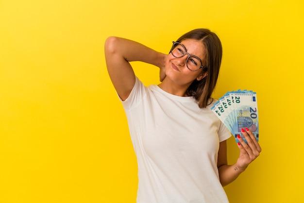 Młoda kobieta kaukaski gospodarstwa rachunki na białym tle na żółtym tle dotykając tyłu głowy, myśląc i dokonując wyboru.
