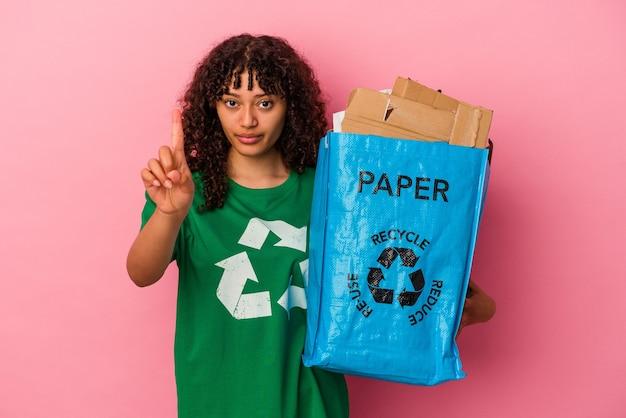 Młoda kobieta kaukaski gospodarstwa recyklingu tworzyw sztucznych na białym tle na różowym tle pokazując numer jeden palcem.