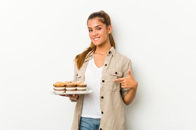 Młoda kobieta kaukaski gospodarstwa słodkie ciasta osoba wskazując ręką na przestrzeni kopii koszuli, dumny i pewny siebie