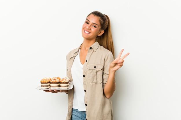 Młoda kobieta kaukaski gospodarstwa słodkie ciasta radosny i beztroski, pokazując symbol pokoju palcami