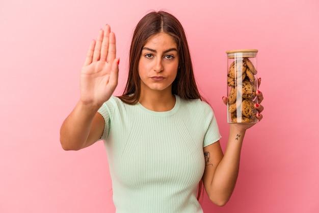 Młoda kobieta kaukaski gospodarstwa słoik ciasteczka na białym tle na różowym tle stojący z wyciągniętą ręką pokazując znak stop, uniemożliwiając.
