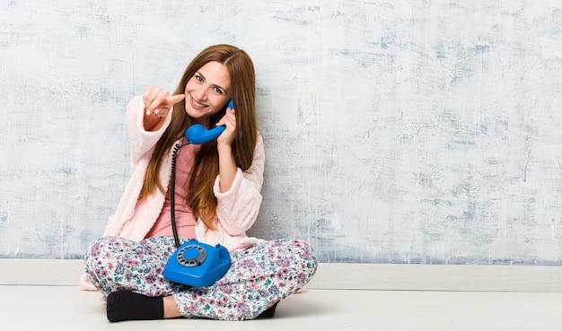 Młoda kobieta kaukaski gospodarstwa wesoły uśmiech na telefon stacjonarny, wskazując na przód.