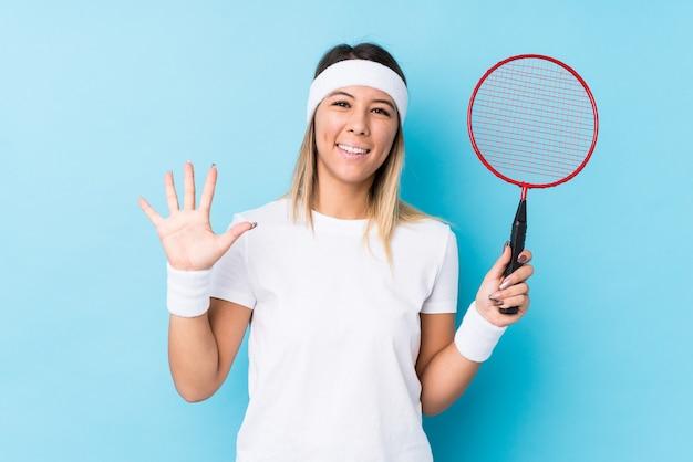 Młoda kobieta kaukaski gra badmintover na białym tle uśmiechnięty wesoły pokazując numer pięć palcami.