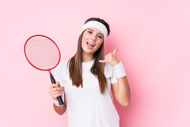 Młoda kobieta kaukaski gra w badmintona na białym tle pokazując gest połączenia telefonu komórkowego palcami.