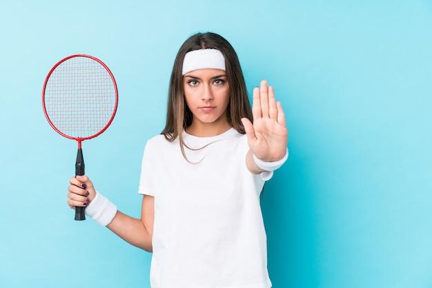 Młoda kobieta kaukaski gra w badmintona na białym tle stojący z wyciągniętą ręką pokazując znak stop, zapobiegając ci.