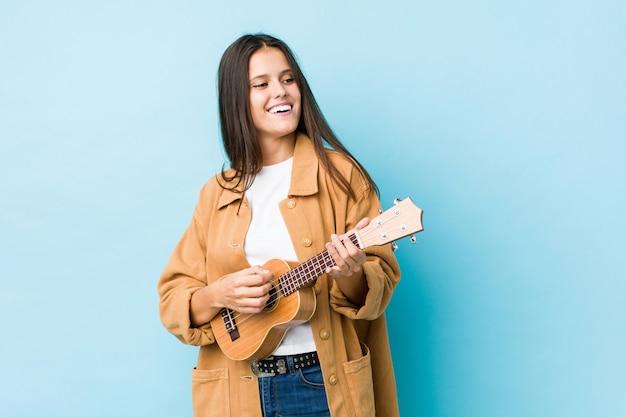 Młoda kobieta kaukaski grając ukelele na białym tle na niebieskiej ścianie