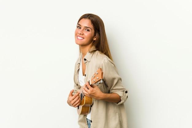 Młoda kobieta kaukaski grając ukelele na białym tle