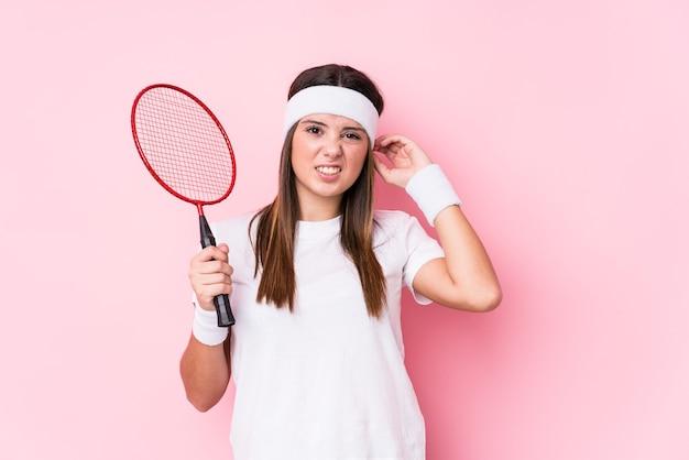 Młoda kobieta kaukaski gry w badmintona na białym tle obejmujące uszy rękami.