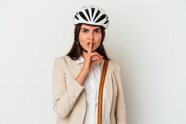 Młoda kobieta kaukaski jedzie na rowerze do pracy na białym tle na białej ścianie, zachowując tajemnicę lub prosząc o ciszę