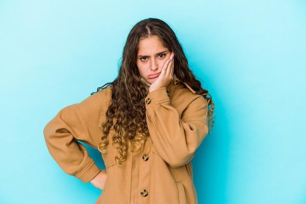 Młoda kobieta kaukaski kręcone włosy na białym tle, która czuje się smutna i zamyślona, patrząc na miejsce.