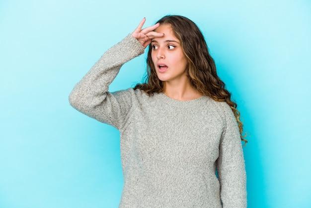 Młoda kobieta kaukaski kręcone włosy na białym tle patrząc daleko trzymając rękę na czole.
