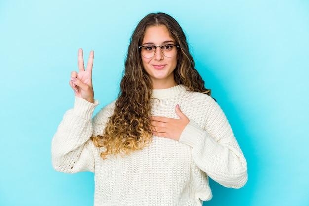 Młoda kobieta kaukaski kręcone włosy na białym tle, składając przysięgę, kładąc rękę na klatce piersiowej.