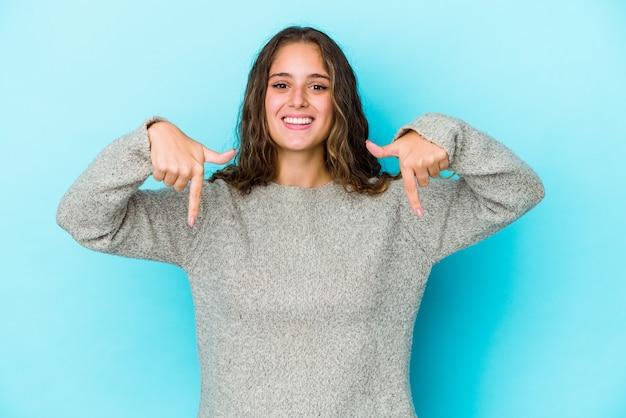 Młoda kobieta kaukaski kręcone włosy na białym tle wskazuje palcami w dół, pozytywne uczucie.