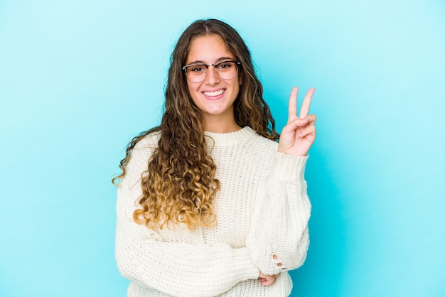 Młoda kobieta kaukaski kręcone włosy na białym tle wyświetlono numer dwa palcami.