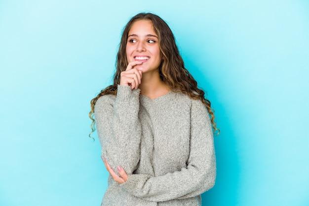 Młoda kobieta kaukaski kręcone włosy na białym tle zrelaksowany, myśląc o czymś, patrząc na przestrzeń kopii.