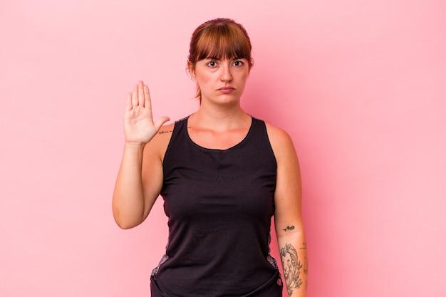 Młoda kobieta kaukaski krzywego uprawiania sportu na białym tle na różowym tle stojąc z wyciągniętą ręką pokazując znak stop, uniemożliwiając.