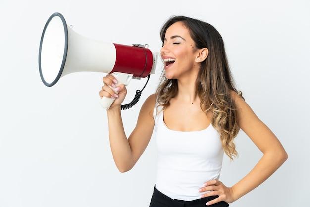 Młoda kobieta kaukaski na białej ścianie krzycząc przez megafon, aby ogłosić coś w pozycji bocznej
