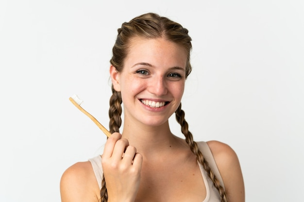 Młoda kobieta kaukaski na białym tle biały szczoteczką do zębów