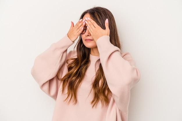Młoda kobieta kaukaski na białym tle boi się zasłaniając oczy rękami.