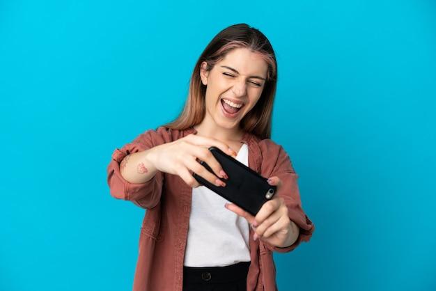 Młoda kobieta kaukaski na białym tle, grając z telefonem komórkowym