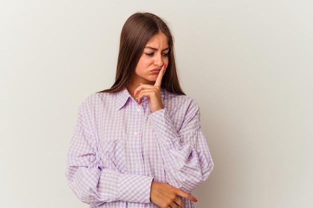 Młoda kobieta kaukaski na białym tle mylić i wątpliwe wzruszając ramionami, aby trzymać miejsce na kopię.