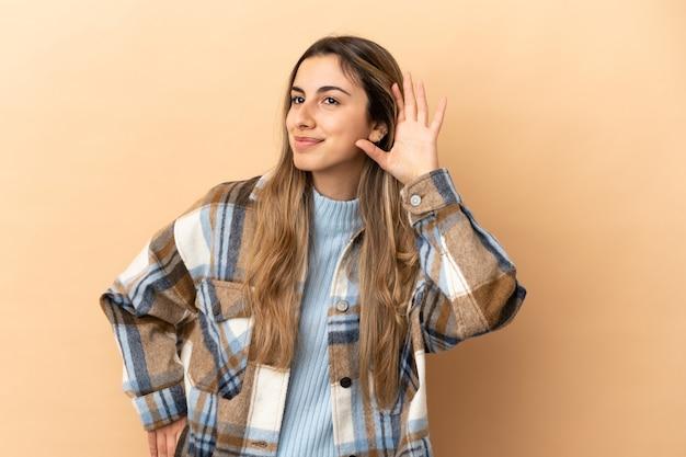 Młoda kobieta kaukaski na białym tle na beżowym tle, słuchając czegoś, kładąc rękę na uchu