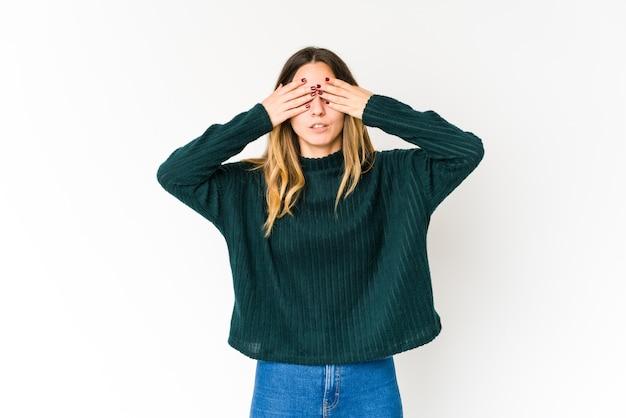 Młoda kobieta kaukaski na białym tle na białej ścianie boi się zakrywających oczy rękami.