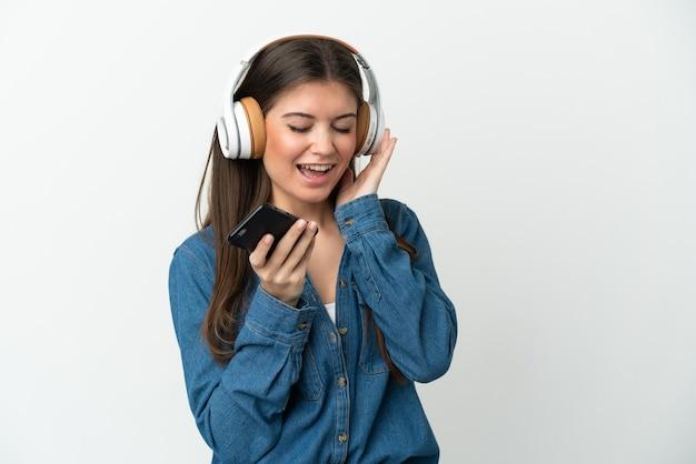 Młoda kobieta kaukaski na białym tle na białej ścianie słuchania muzyki z telefonu komórkowego i śpiewu
