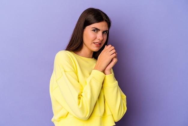 Młoda kobieta kaukaski na białym tle na fioletowej ścianie przestraszony i przestraszony.