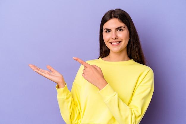 Młoda kobieta kaukaski na białym tle na fioletowym tle podekscytowany, trzymając miejsce na dłoni.