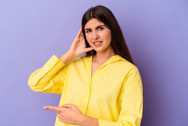 Młoda kobieta kaukaski na białym tle na fioletowym tle próbuje słuchać plotek.