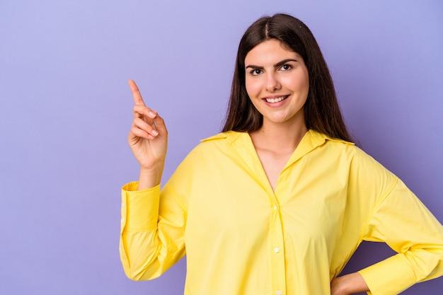 Młoda kobieta kaukaski na białym tle na fioletowym tle uśmiechając się radośnie wskazując palcem wskazującym.