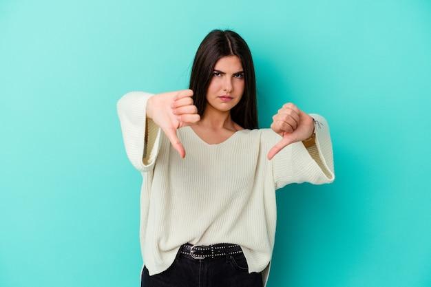 Młoda kobieta kaukaski na białym tle na niebieskiej ścianie pokazując kciuk w dół i wyrażając niechęć.