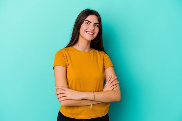 Młoda kobieta kaukaski na białym tle na niebieskiej ścianie, śmiejąc się i zabawy