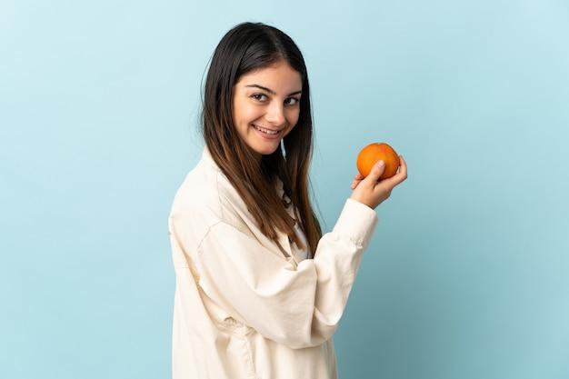 Młoda kobieta kaukaski na białym tle na niebieskiej ścianie trzyma pomarańczowy
